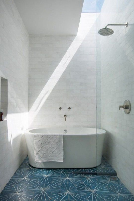 bold and stunning tile floors in blue modern white bathtub wall mounted shower head white walls clear glass wall partition