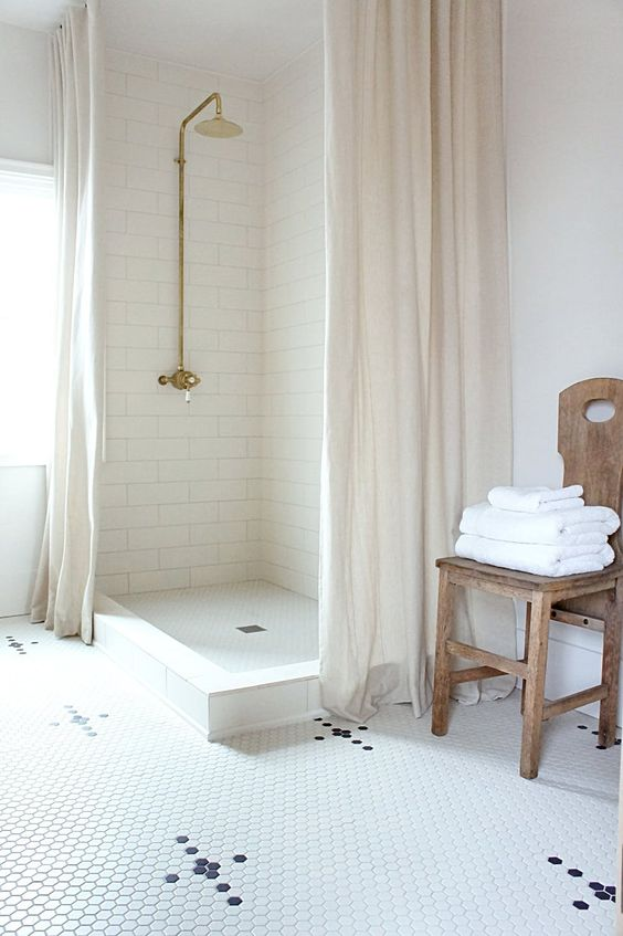 chic walk in shower idea with brass finish shower head natural wood chair small hexagon tile floors with black accent