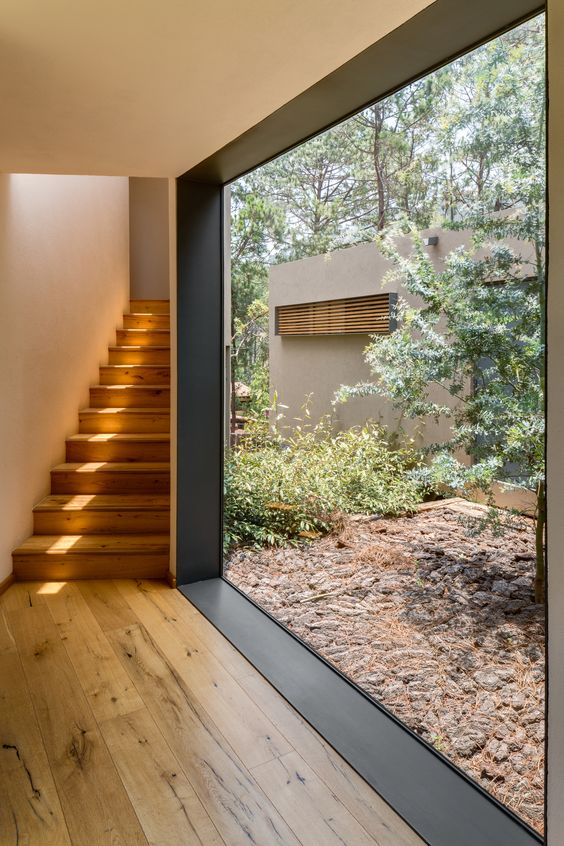 clean and minimalist interior with wood floors wood stairs large glass window