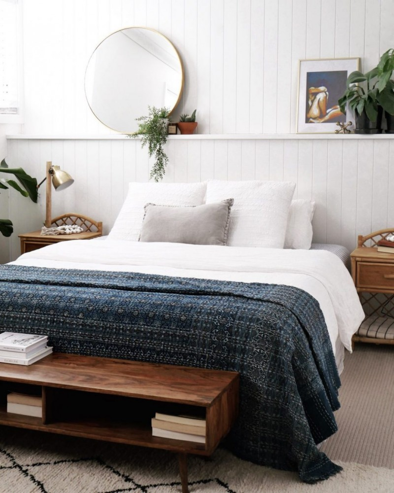 coastal bedroom idea navy blue blanket in textural color crisp white comforter crisp white bed linen crisp white pillow hardwood bed bench with under storage round mirror greenery