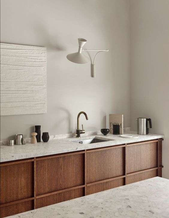 crisp white walls with white wall decor and white sconce white marble countertop with sink and brass faucet kitchen counter with organic wood panels