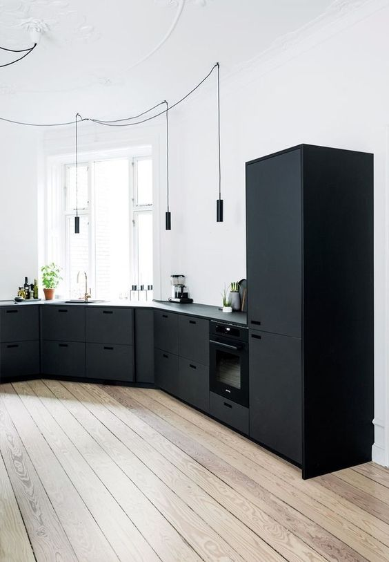 curved black kitchen countertop and cabinets crisp white walls wood plank floors modern black pendants