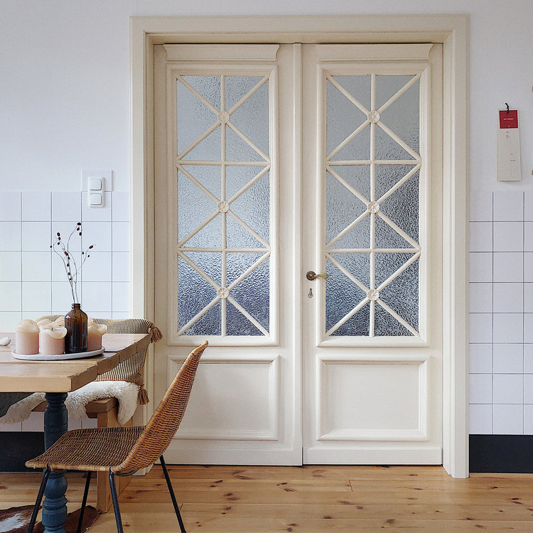 door panel with blurred glass and geometric texture trims in white white ceramic tile walls light wood floors