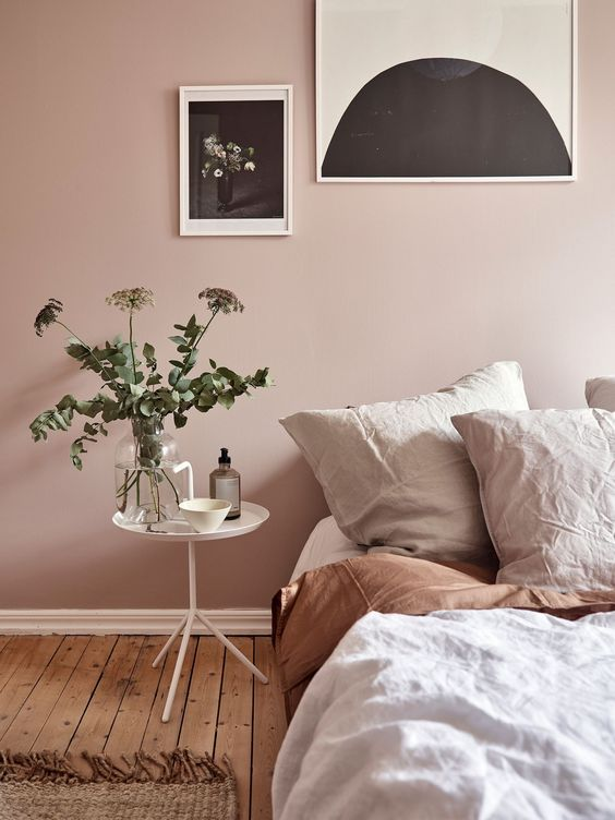 dusty pink wall white bedside table light tone bedding treatment wall decors dominated by black wood plank floors