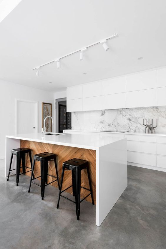 flat surface cabinets on top marble backsplash white kitchen island with sink and faucet black stools wood panel under the kitchen island