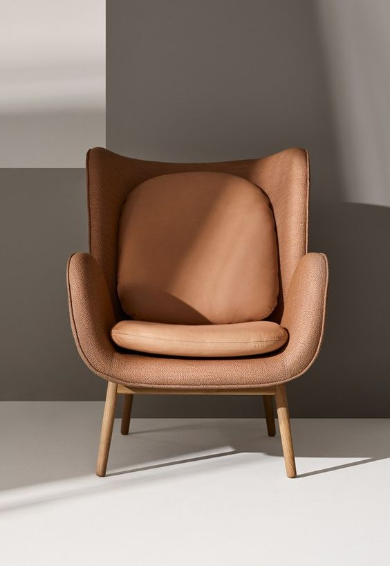 futuristic design accent chair with wood tapered legs and soft neutral upholstery