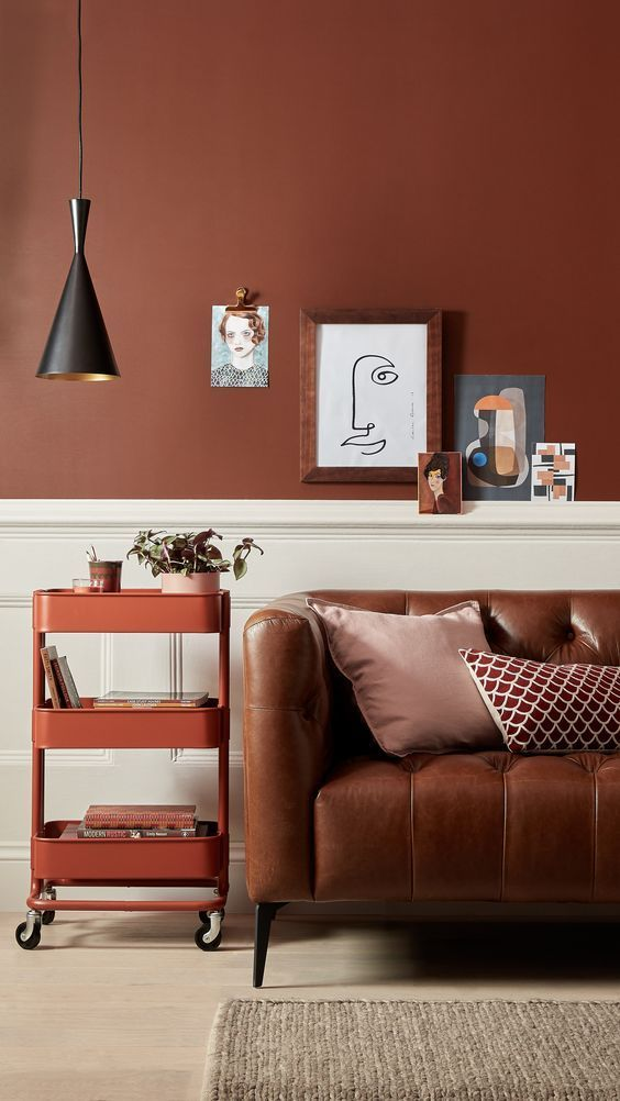 half bold terracotta half white walls natural brown leather sofa movable cart for books gray area rug accent black pendant