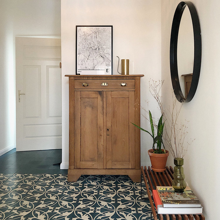 half way tile floors with white classic geometric patterns wooden closet wood bench seat big size round mirror with black frame
