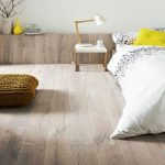 Half Way Wood Cladding Wall Light Wood Plank Floors Small Bedside Table With White Top White Bedding Treatment Yellow Pillow Knitted Floor Pillow In Mustard