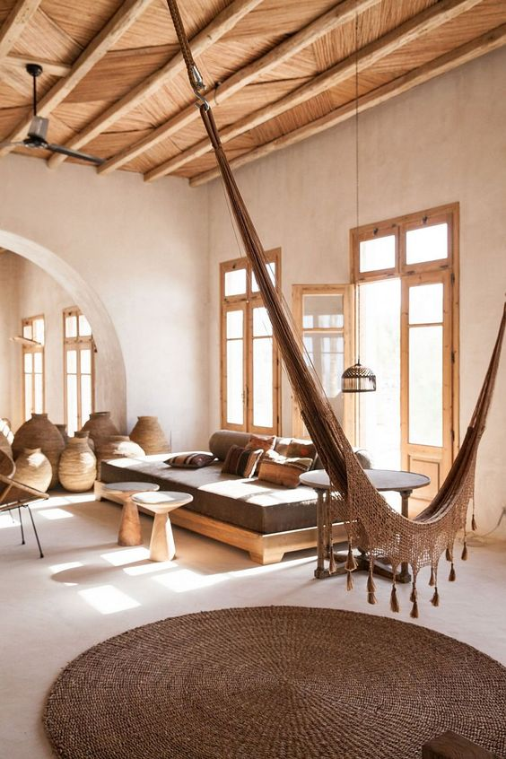 inspiring living room in Greece Island wooden ceilings with exposed wood beams earthy brown hammock wood frame daybed with milo toned cushions wood framed glass windows and door