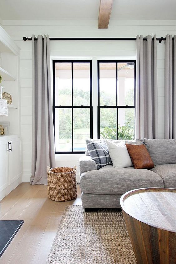 light gray window draperies glass windows with black trims light wood floors flat woven rug ornate woven basket unique wood coffee table