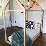 Light Wood Floor Bed Frame For Toddler With Colorful Pompoms Modern Industrial Light Fixture And Green Velvet Throw Blanket
