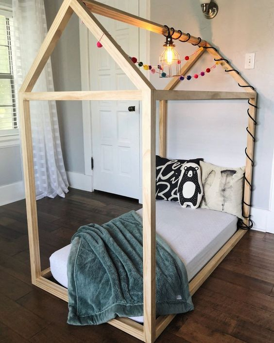 light wood floor bed frame for toddler with colorful pompoms modern industrial light fixture and green velvet throw blanket
