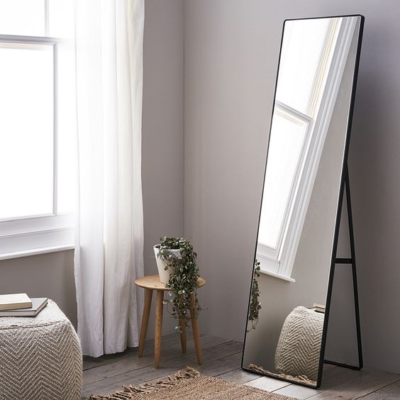 light wood stool with potted greenery free standing mirror with black wood finish frame flat woven runner white pouf chair whitewashed wood plank floors dramatically white draperies