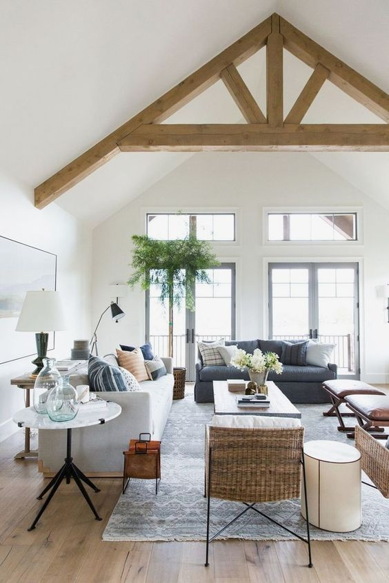 open concept interior idea with wooden beams white vaulted ceilings modern living room furniture light gray area rug round top side table light wood floors