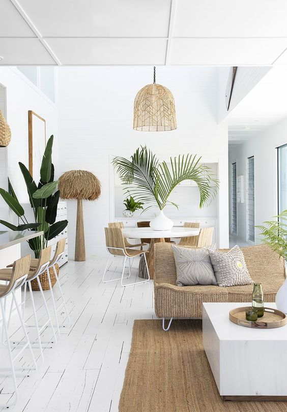 open concept interior in contemporary style white wood plank floors oversize pendant with natural material lampshade natural material sofa with light tone throw pillows houseplants in woven pot