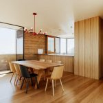 Open Concept Space Connecting The Dining Space And Kitchen Modern Style Wood Dining Chairs And Dining Table Black Dining Chairs Wood Floors Wood Walls Accent Chandelier In Red
