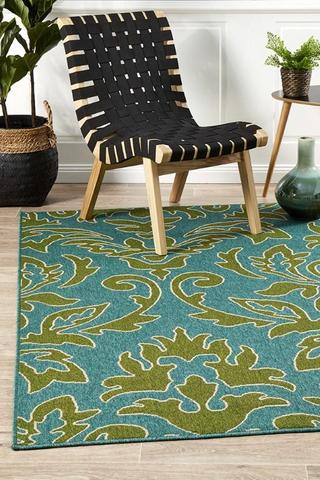 outdoor rug with green floral motifs and blue color backdrop wooden chair with rubber belt upholstery in black
