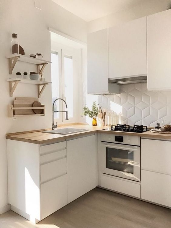 small modern kitchen with crisp white cabinets light wood countertop and floors white backsplash with geometric patterns