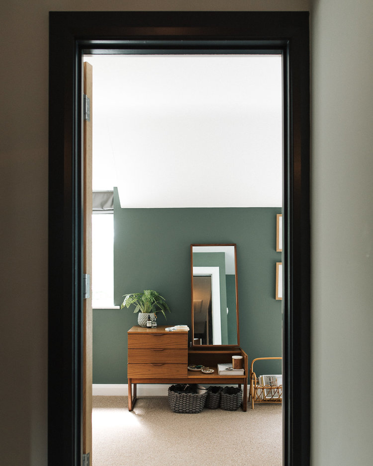smoke green walls white ceilings wooden bedroom vanity with cabinet system and wood framed mirror