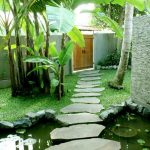 Stone Pathway Artificial Pond With Stone Frame Bed Of Green Grass Tropical Plants