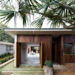 Ultra Modern Exterior With Dark Wood Walls And Front Door Log Tree Planter
