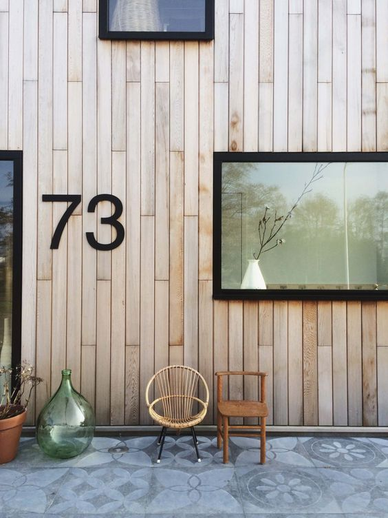 vertical way wood cladding exterior walls with black framed glass windows and door