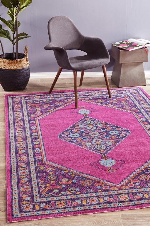 vintage Persian area rug in pink and blue midcentury modern chair with wood legs woven planter houseplant