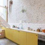 White Countertop Yellow Cabinets White Subway Tile Backsplash Rough Surface Brick Walls In Crisp White Gray Floors