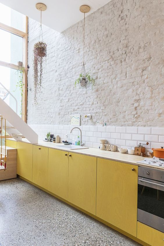 white countertop yellow cabinets white subway tile backsplash rough surface brick walls in crisp white gray floors