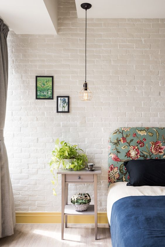 white crisp brick walls vividly beautiful floral headboard light gray nightsand with greenery modern industrial pendant black framed wall decors