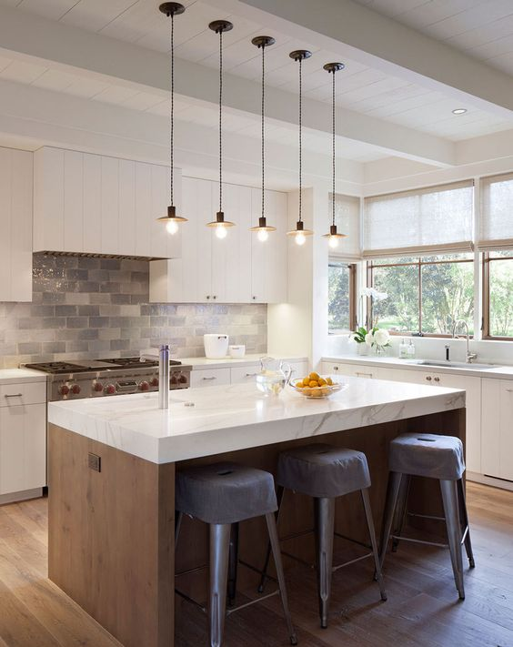white marble kitchen island gray plastic stools with gray covers flat surface cabinets in white stone like tile backsplash modern rustic pendants