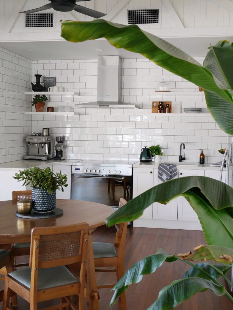 white subway tile walls open shelving units in white white countertop stainless steel kitchenware wooden dining furniture