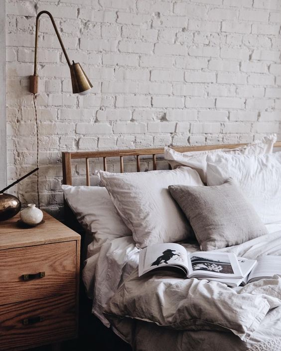 white vibrant brick walls wood bed frame with headboard wooden nighstand with drawer system dusty white bedding treatment gold toned wall sconce