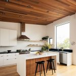 White Walls White Flat Surface Cabinets Black Countertop White Kitchen Island With Wood Panel Underneath Modern Black Bar Stools Huge Glass Window Wood Floors