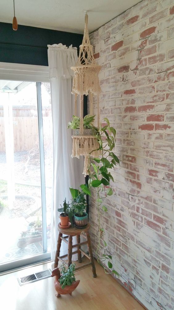whitewashed brick wall some greenery hanging macrame white crisp white draperies light wood floors