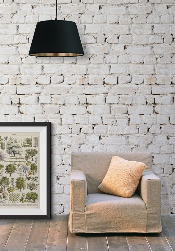 whitewashed brick wallpaper idea pendant with oversized black lampshade leaning painting with black frame neutral tone sofa with pastel throw pillow