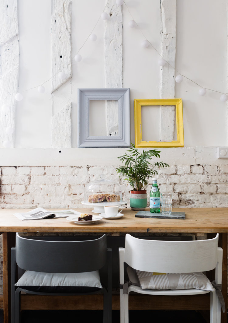 Duck Goose Coffee Shop interior with whitewashed brick walls coloful ornate frames natural wood table modern chairs in white and black