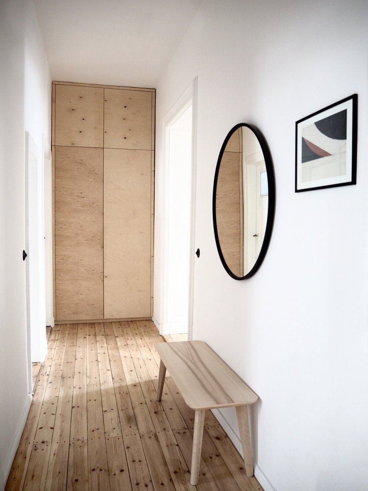 Scandinavian hallway idea light wood floors light wood bench seat black framed wall mirror in round shape crisp white walls
