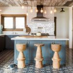Adorable Wooden Stools With Unique Shape Dark Tile Floors With Geometric Patterns White Subway Tile Walls Marble Countertop Kitchen Island With Blue Base And White Top Modern Industrial Pendants