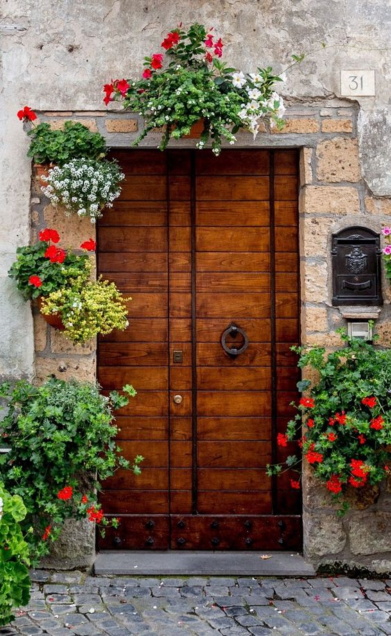 antique front door made from hard wood greenery with blooming flowers