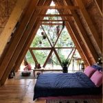 Attic Bedroom In Big Size Purple Bed Linen And Pillows Deep Blue Duvet Cover Multicolored Rug Small Sitting Area Glass Window With Triangle Wood Trims