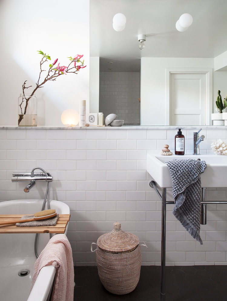 bathroom with white subway tile walls frameless mirror white bathtub standing bathroom sink in white dark floors