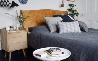 bed frame with hardwood headboard light wood nightstand in scandinavian style gray bed linen black wood plank floors mini runner with geometrical patterns white round top table with wood legs