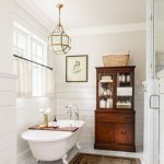 Clawfoot Tub In White Antique Hutch Modern Pendant With Brass Accents Half Way Curtains In White Vintage Area Rug