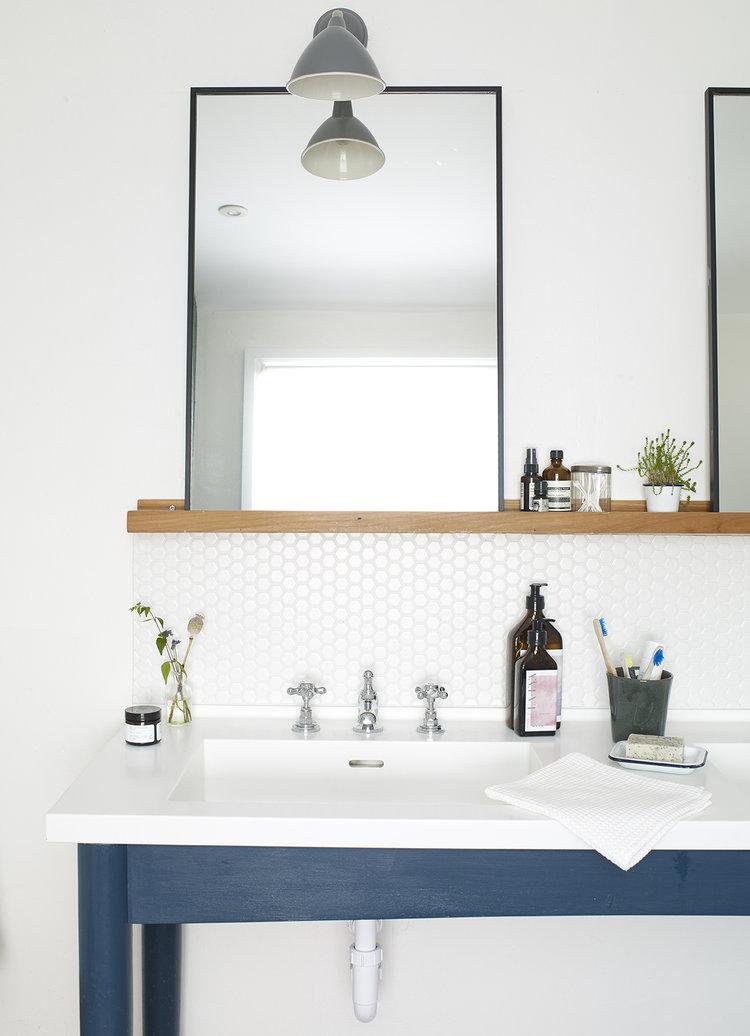 clean and modern bathroom black framed mirror hexagon tile backsplash white countertop with modern sink single wooden shelving unit