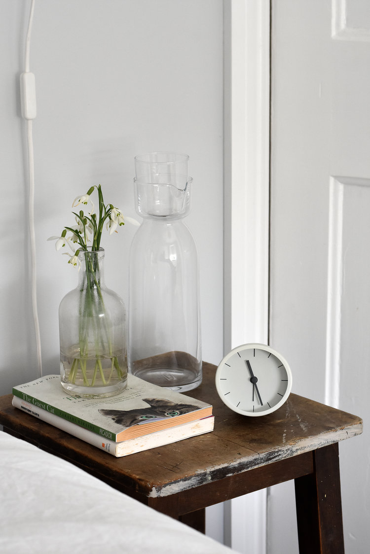 dark finish wood bedside table with waker clock fresh flowers on ornate glass vase and some books