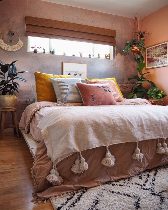 dusty pink duvet cover with white linen top and tassels colorful pillows