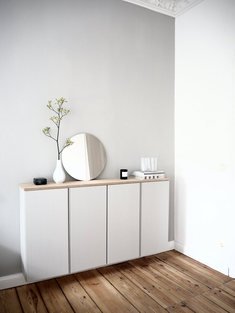 floating dresser with flat doors and light wood top frameless round shaped mirror organic wood plank floors crisp white walls