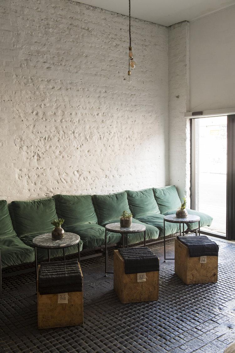 green velvet seats round top tables wooden cube seats textured white walls black tile floors